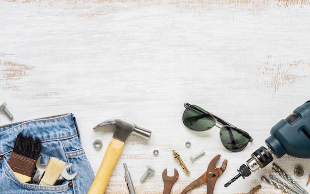 Accesorios planos de la endecha herramientas y ropa para el trabajador en de madera blanco oxidado con el espacio de la copia. vista superior del espacio en blanco para el trabajo o el día del trabajo, el día del trabajador, el día del padre y el concepto de reparación del hogar diy.