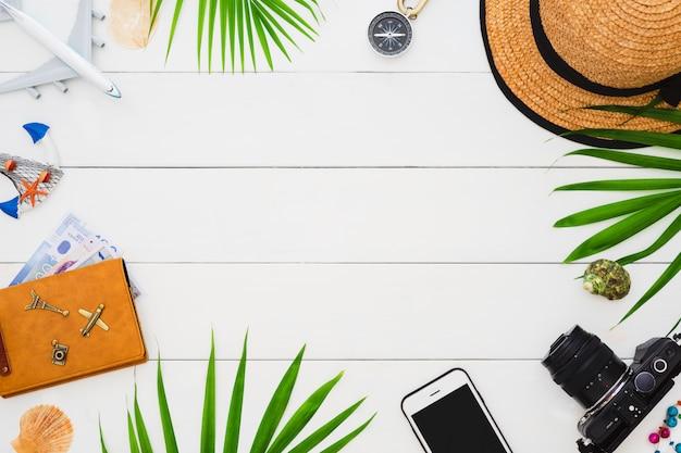 Accesorios planos del viajero de la endecha en el fondo de madera blanco. concepto de viajes y vacaciones de horario de verano.