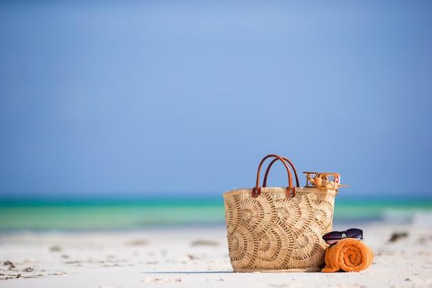 Accesorios de playa: avión de juguete, bolsa de paja, toalla de color naranja y gafas de sol en la playa