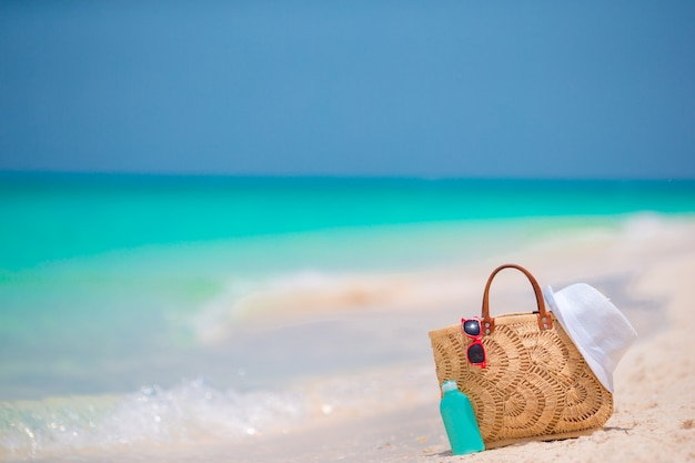 Accesorios de playa: bolsa de paja, sombrero blanco y gafas de sol rojas en la playa