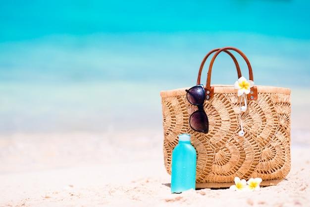 Accesorios de playa: bolso de paja, auriculares, botella de crema y gafas de sol en la playa.