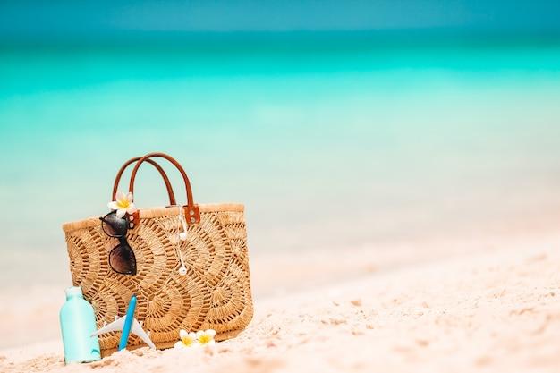 Accesorios de playa: bolso de paja, sombrero y anteojos en la playa