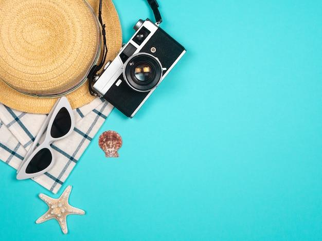 Accesorios de playa, cámara de película retro, gafas de sol, sombrero de playa de estrella de mar y concha de mar sobre fondo azul para vacaciones de verano y vacaciones