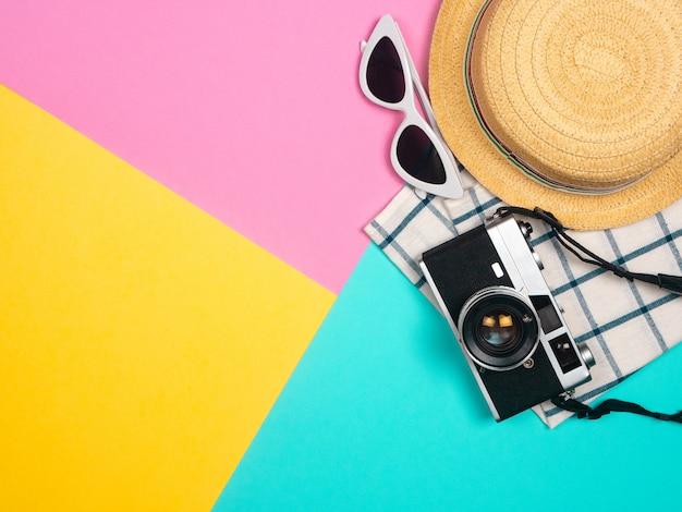 Accesorios de playa, cámara retro, gafas de sol, sombrero de playa de estrella de mar y concha de mar sobre fondo azul, rosa y amarillo para vacaciones de verano