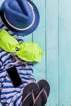 Accesorios de playa con traje de baño amarillo, lentes oscuros y chanclas.