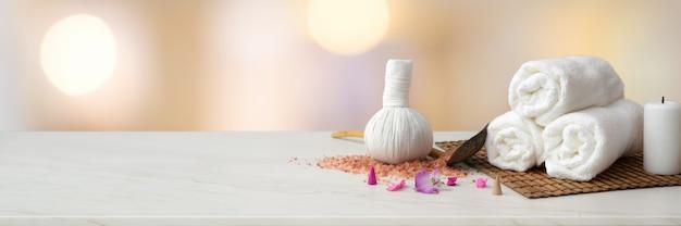 Accesorios de spa con toalla blanca, vela, bola de compresión a base de hierbas y espacio de copia