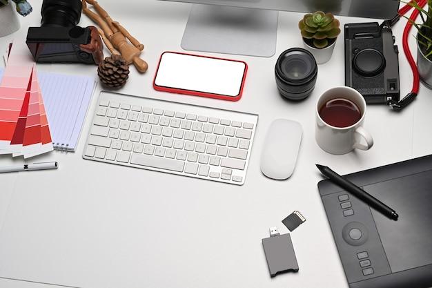 Accesorios para teléfonos inteligentes, tabletas gráficas y cámaras en el lugar de trabajo del diseñador creativo.