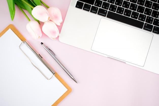 Los accesorios de trabajo para mujeres se encuentran planos sobre papel rosa pastel.