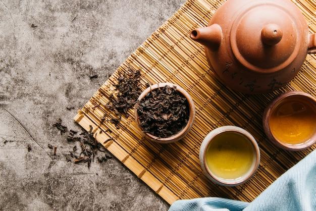 Accesorios tradicionales para la ceremonia del té con tetera y taza de té en mantel individual