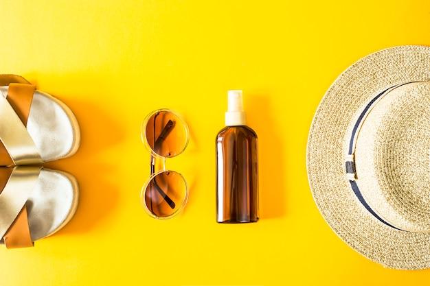 Accesorios de verano para mujeres para unas vacaciones de playa con un sombrero de paja, gafas de sol y protector solar sobre un fondo amarillo.