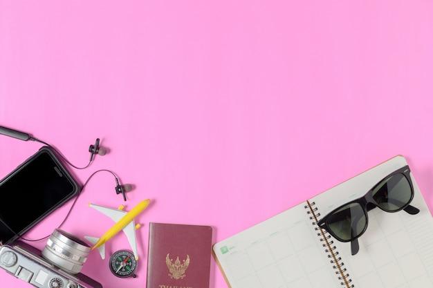 Accesorios para viajar en fondo rosa, viajes de verano
