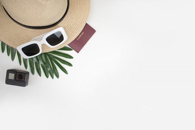 Accesorios de viaje para jóvenes viajeras con un pasaporte blanco sobre la mesa y hojas de verano.