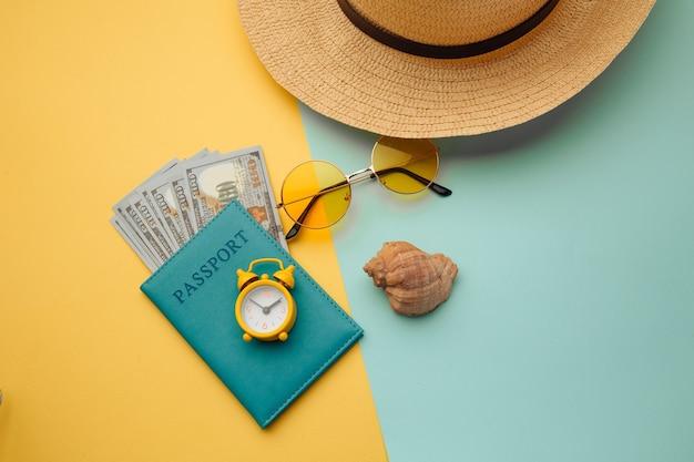 Accesorios de viaje y pasaporte con dinero sobre una superficie coloreada