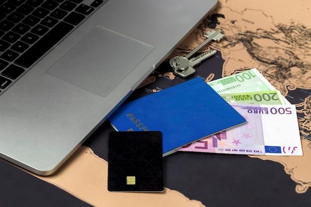 Accesorios de viaje, pasaporte y tarjeta de crédito cerca de la computadora portátil en el mapa