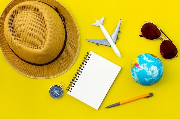 Accesorios de viajero laicos planos sobre fondo amarillo con espacio en blanco para texto. vista superior concepto de viaje o vacaciones. fondo de verano