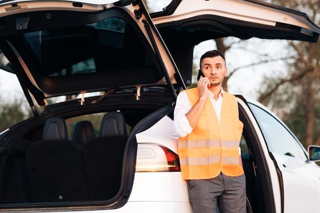 Accidente automovilístico en la carretera. hombre con chaleco reflectante llamando por teléfono sobre avería en su coche eléctrico