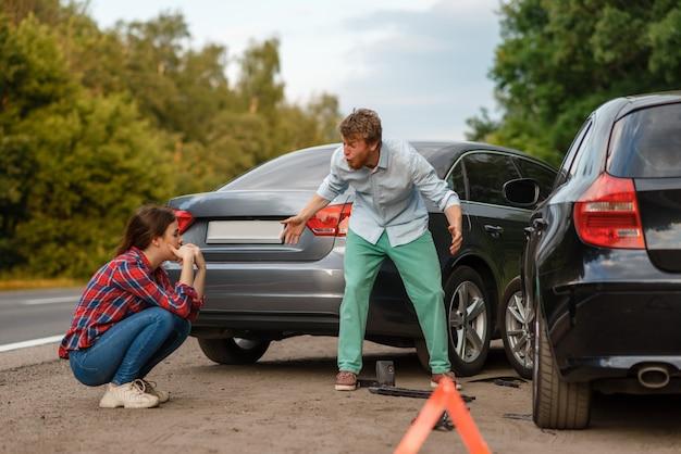 Accidente automovilístico en la carretera, se solucionan conductores masculinos y femeninos. accidente automovilístico, señal de parada de emergencia. automóvil roto o vehículo dañado, colisión de automóviles en la carretera