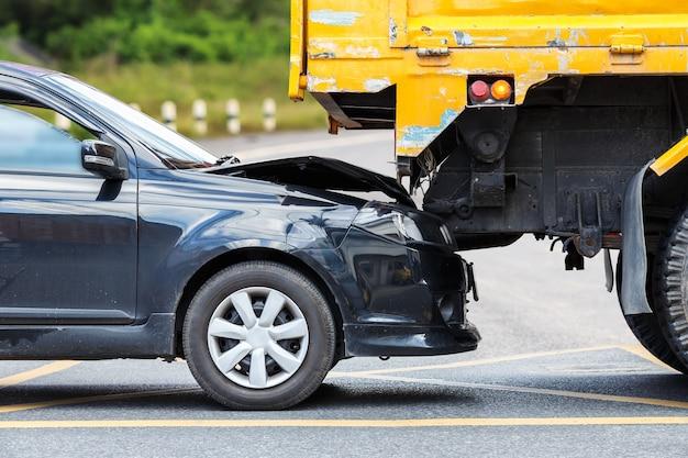 Accidente en el camino que implica el coche negro y el camión amarillo en phuket, tailandia