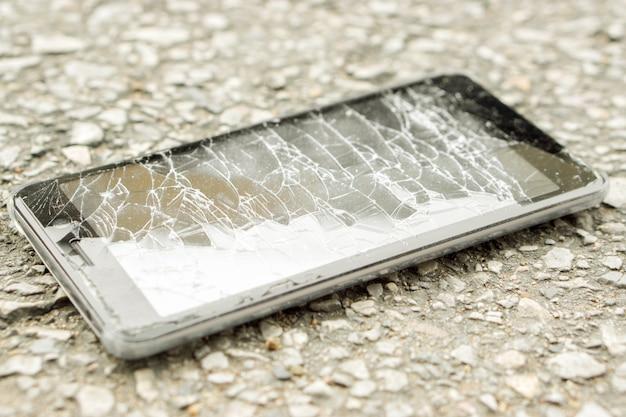 El accidente negro del teléfono móvil del primer cae al camino y al vidrio roto con la luz natural del sol.