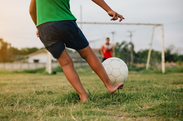 Acción deportiva al aire libre de un grupo de niños divirtiéndose jugando fútbol soccer para hacer ejercicio