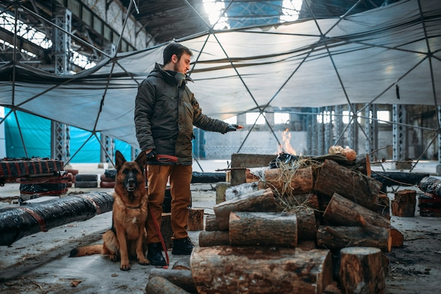 Acechador con su animal doméstico contra la chimenea, el hombre vive en un mundo postapocalíptico. estilo de vida post-apocalipsis en ruinas, día del juicio final, día del juicio