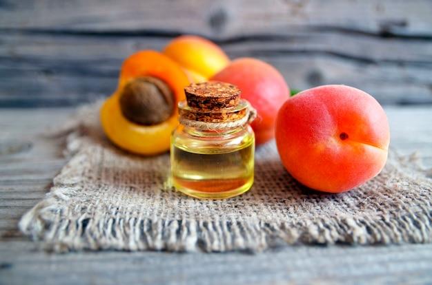 Aceite de albaricoque de granos de albaricoque en un frasco de vidrio y albaricoques maduros frescos en la mesa de madera vieja.