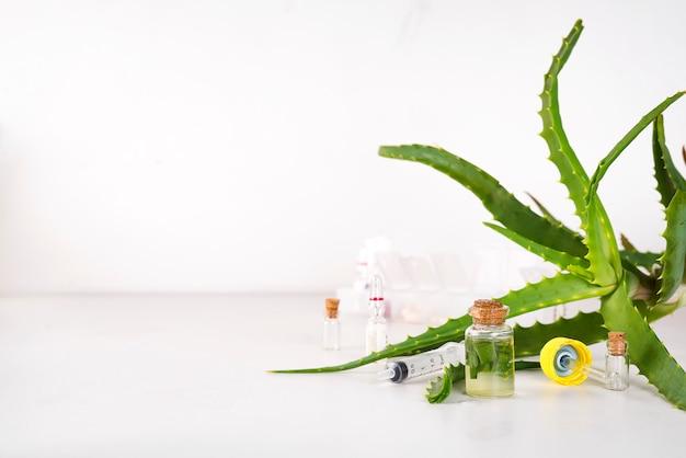 Aceite de aloe vera en botella de vidrio con rodajas de gel de aloe vera