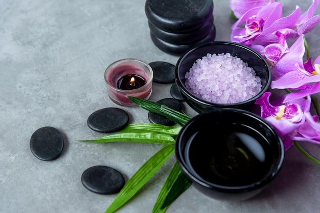 Aceite de aromaterapia de naturaleza orquídea púrpura flor spa con velas y spa de piedra.