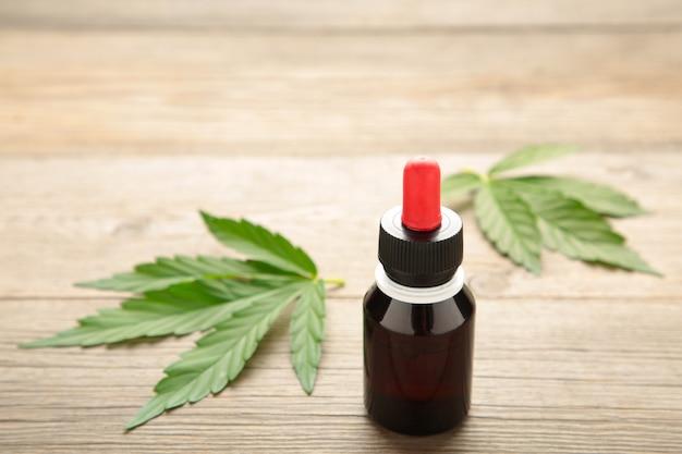 Aceite de cáñamo y hoja de cannabis en madera gris. aceite de cannabis saludable.