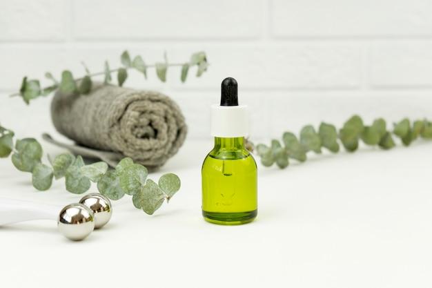 Aceite de cbd para masaje facial y rodillo facial acostarse sobre una mesa blanca