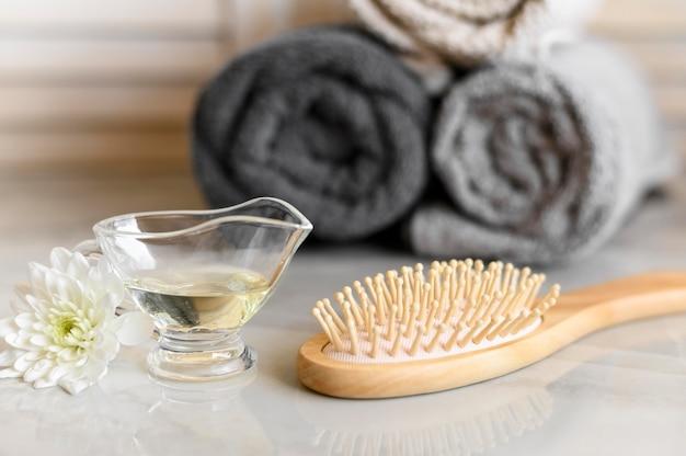 Aceite y cepillo para el cuidado del cabello en el escritorio