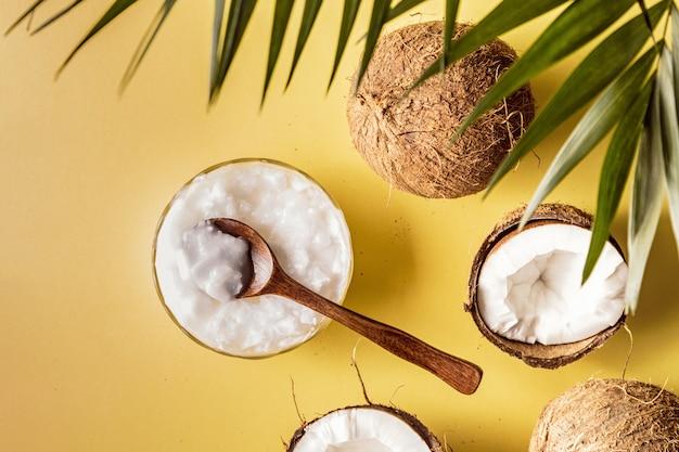 Aceite de coco y cocos en una con hojas tropicales.