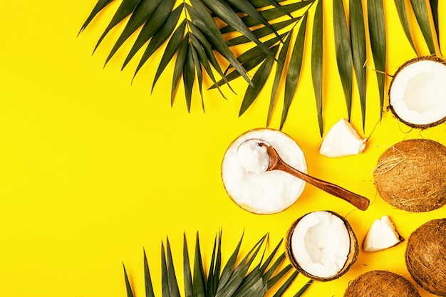 Aceite de coco y cocos sobre un fondo con hojas tropicales