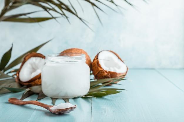 Aceite de coco y cocos sobre un pastel brillante