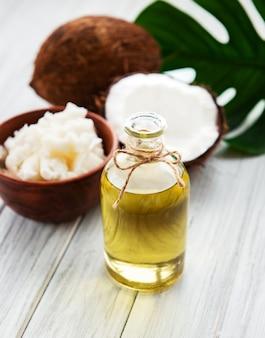 Aceite de coco fresco y cocos en una vieja mesa de madera