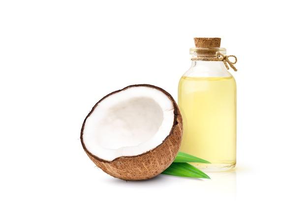 Aceite de coco con frutos de coco cortado por la mitad aislado sobre fondo blanco.