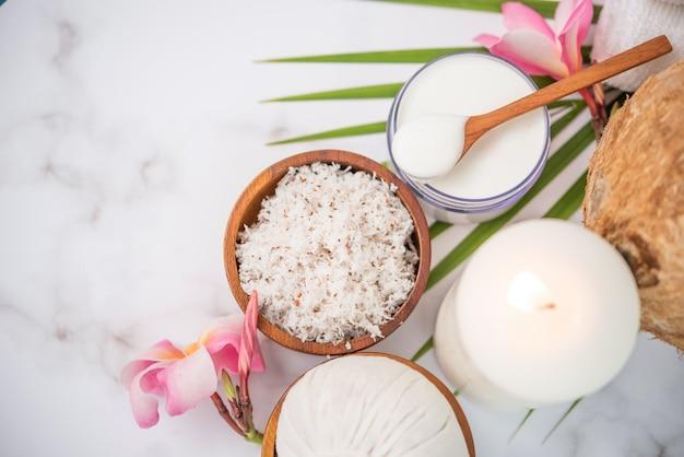 Aceite de coco, hojas tropicales y cocos frescos. productos de coco spa en superficie de madera clara.