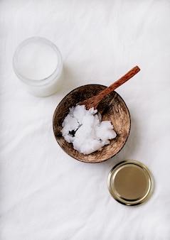Aceite de coco orgánico en el frasco de vidrio y en el tazón de coco con cuchara de coco. concepto de sostenibilidad. vista superior. lay flat.