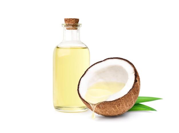 El aceite de coco que gotea del coco cortado por la mitad con una botella aislada en la superficie blanca