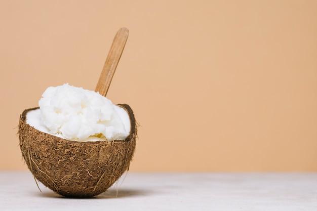 Aceite de coco en un tazón de coco con espacio de copia