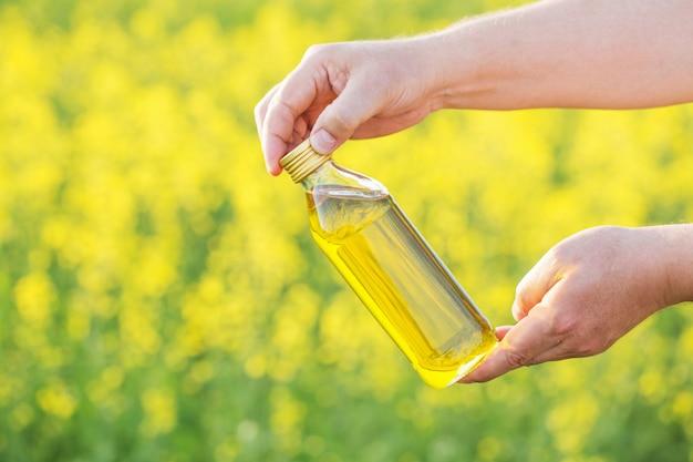 Aceite de colza en botella en mano en campo de violación de pared
