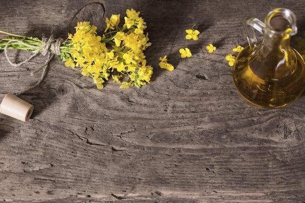 Aceite de colza (canola) y flores de colza en mesa de madera