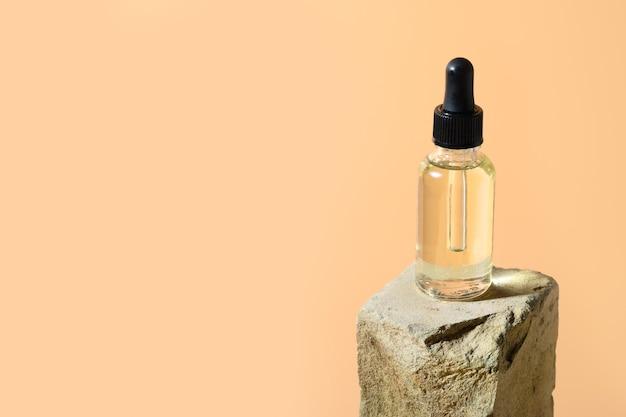Aceite cosmético de belleza en botella de vidrio en el podio de piedra en el espacio beige