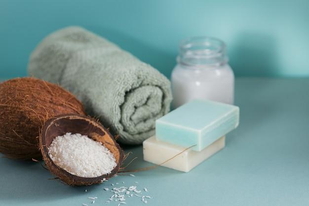 Aceite cosmético de coco orgánico y jabón natural artesanal con coco y copos de coco en color azul.