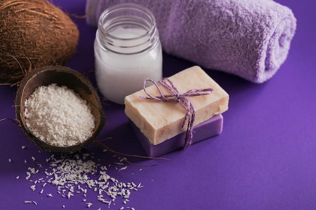 Aceite cosmético de coco orgánico y jabón natural hecho a mano con coco y copos de coco sobre fondo de color púrpura
