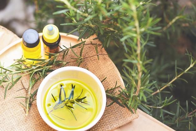 Aceite esencial de aceite de romero de botella de aceite esencial de romero para aromaterapia y planta de hoja de romero en el fondo - cosmética orgánica con extractos de hierbas