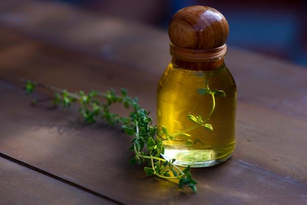 Aceite esencial de albahaca en una botella con ramas frescas de albahaca