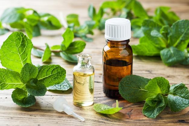 Aceite esencial de aroma con menta sobre fondo de madera.