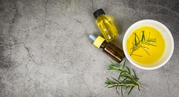Aceite esencial de botella de aceite esencial de aceite de romero para aromaterapia y hoja de romero sobre fondo gris - cosmética orgánica con extractos de hierbas, vista superior