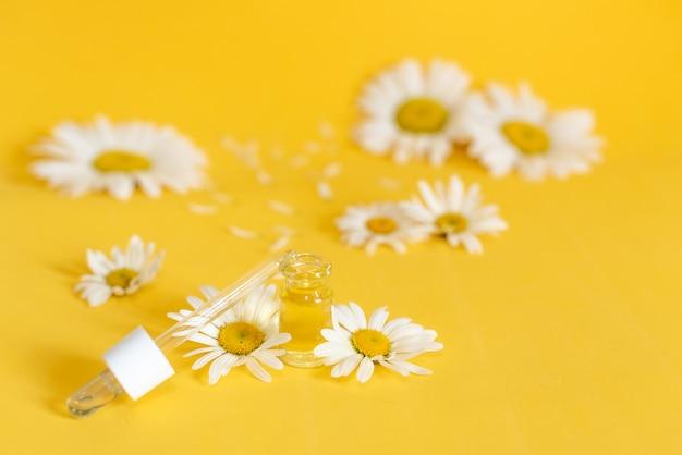 Aceite esencial en botella de vidrio con flores de manzanilla frescas.